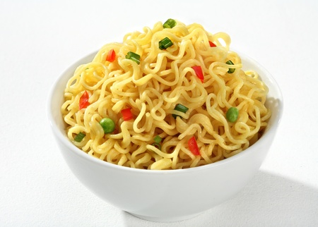 low cal: Bowl with cooked noodles - vermicelli flavored with green peas and chopped bell pepper in a white bowl - on white background