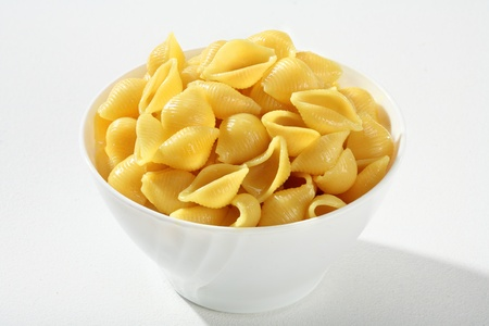 low cal: Cooked pasta shells - a portion of cooked pasta, served without sauce on a white ceramic bowl against a white backdrop Stock Photo