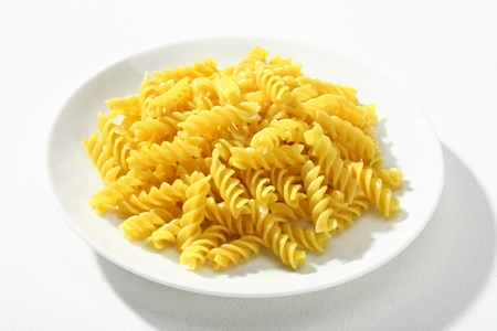 low cal: Cooked macaroni - a portion of cooked macaroni, served without sauce on white plate against a white backdrop