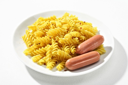 low cal: Cooked macaroni   sausages - a portion of cooked macaroni, served with sausages on white plate against a white backdrop