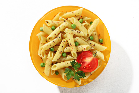 short pasta: Looking down at a plate of cooked tubular pasta with seasoning herbs - top view of flavored macaroni noodles served with green parsley and tomato in an orange plate