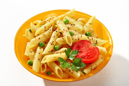 short pasta: Delicious cooked tubular pasta dish - a portion of cooked macaroni noodles served with green parsley and tomato in an orange plate