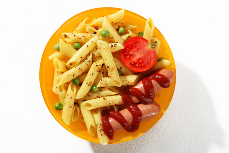 short pasta: Expertly cooked reginelle - a portion of cooked macaroni noodles served with green parsley, tomato and sausages in an orange plate