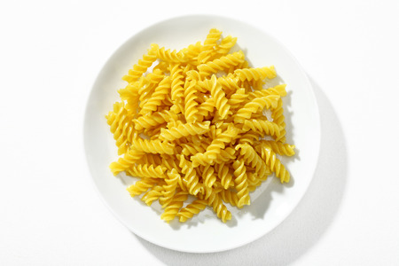 low cal: Looking down at a plate of properly cooked pasta - top view of macaroni noodles on white ceramic plate