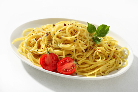 low cal: Amazing spaghetti - a portion of cooked spaghetti pasta served with greens and tomatoes on white ceramic plate