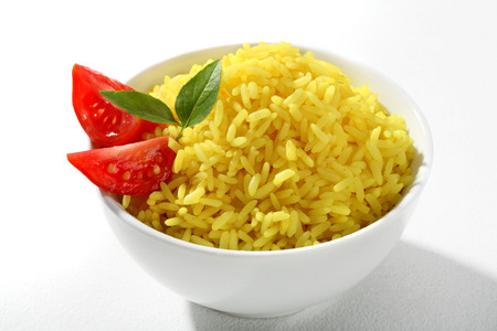 low cal: Yellow rice dish - a portion of cooked yellow rice served with greens and tomatoes in white ceramic bowl