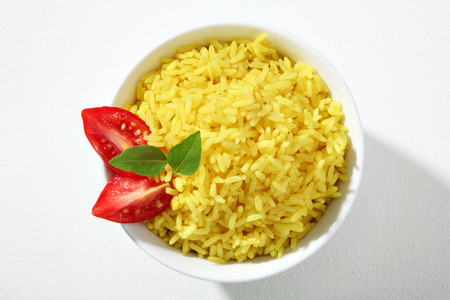 cooked rice: Looking down at a bowl of yellow rice dish - top view of cooked yellow rice served with greens and tomatoes in white ceramic bowl