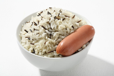 caloric: Black   white rice with frankfurter - a portion of cooked black and white rice with sausage in white ceramic bowl Stock Photo