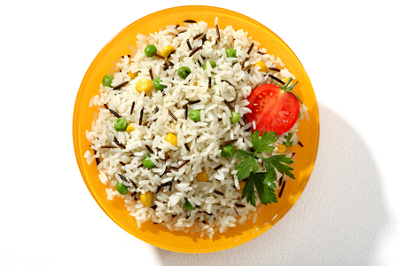 low cal: Looking down at a plate of black   white rice dish - top view of cooked black and white rice served with greens and tomato in an orange plate