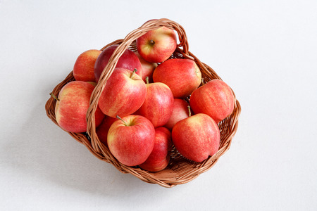 beauteous: Apple picking season - studio photography of ripe apples in a wicker basket - on white background Stock Photo