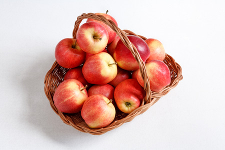 beauteous: Apple harvest - studio photography of a basket with red ripe apples - on white background