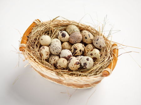Quail eggs nutrition - studio shot of quail eggs in a wicker basket - on white background photo
