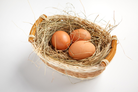 beauteous:  Basket with brown chicken eggs - studio photography of brown chicken eggs in a wicker basket - on white background Stock Photo