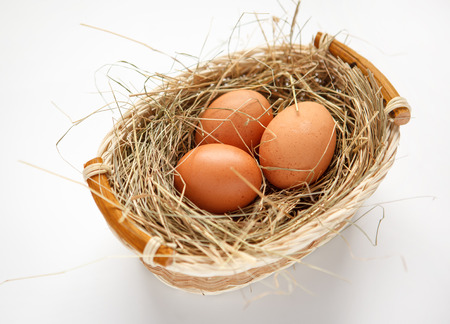 beauteous: Wattled willow basket with brown chicken eggs - HQ studio photo of brown chicken eggs in a wicker basket - on white background