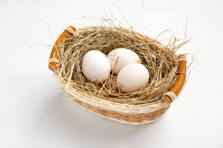 Basket with white chicken eggs - studio photography of white chicken eggs in a wicker basket - on white background photo