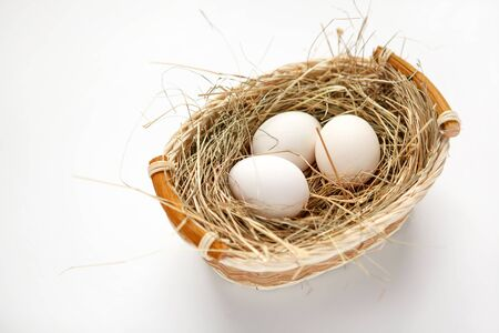 beauteous: Wattled willow basket with white chicken eggs - HQ studio photo of white chicken eggs in a wicker basket - on white background