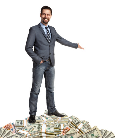 money pile: Happy businessman shows the way how to make a lot of money - hospitable person standing on a pile of banknotes - isolated on white background