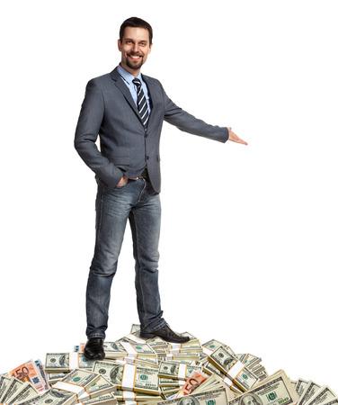 mucho dinero: Hombre de negocios feliz muestra la forma en cómo hacer un montón de dinero - hospitalario persona de pie sobre una pila de billetes - aislados en fondo blanco