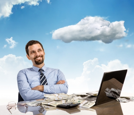 cfo: Daydreaming businessman with arms crossed - cheerful and successful businessman smile day dreaming with his arms crossed sitting at his desk with laptop and a lot of money Stock Photo
