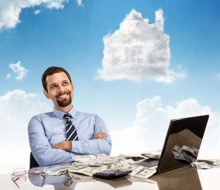good investment: Daydreaming businessperson with arms crossed - happy guy smile day dreaming with his arms crossed sitting at his desk with laptop and a lot of money