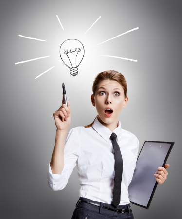 Found a way out - attractive woman wearing a white shirt with a tie and a folder in her hand enthusiastic about the idea - on grey background photo