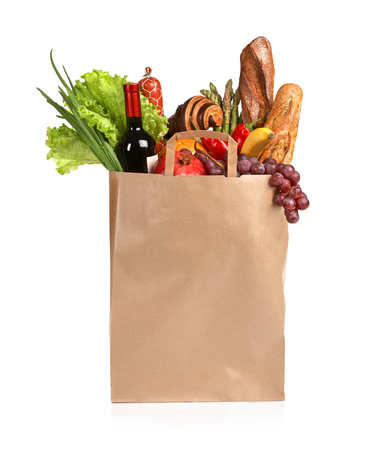 Grocery shopping - studio photography of brown grocery bag with fruits, vegetables, bread, bottled beverages - isolated over white background photo