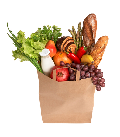 Bag full of healthy food - studio photography of brown grocery bag with fruits, vegetables, bread, bottled beverages - isolated over white background photo