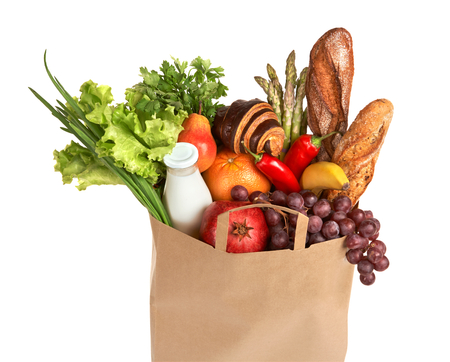A grocery bag full of healthy fruits and vegetables - studio photography of assorted foods in brown grocery bag isolated over white background photo