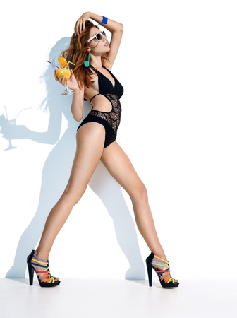 beachwear: Stay stylish - photo of glamor girl in black beachwear with orange juice