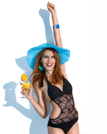 beachwear: Hell yeah - stock image of joyful woman in black beachwear with refreshing summer drink in her hand on white background