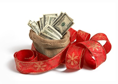 Bag of money - studio photography of bag full of hundred dollar bills, decorated with red Christmas ribbon Stock Photo