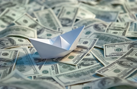 Origami paper boat at sea of money - studio photography of american moneys of hundred dollar on background