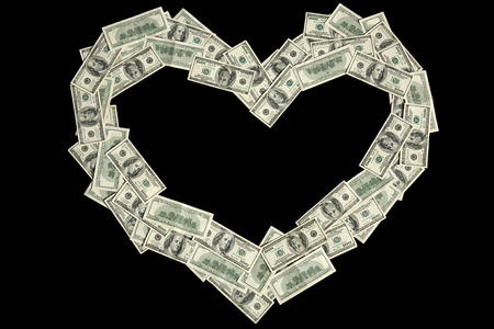 Money in a shape of heart - studio photography of american moneys of hundred dollar on black background photo