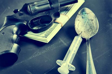 delincuencia: Pedazo de evidencia de una pistola, una jeringa, cuchara y dinero en el fondo negro Foto de archivo