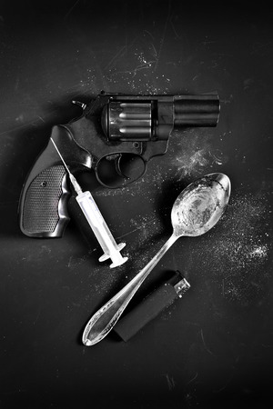 wrongdoing: Criminal tools of a gun, syringe, spoon and lighter on black background