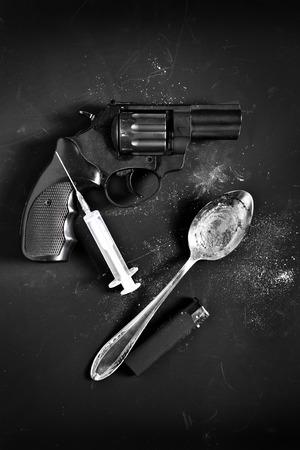 delincuencia: Herramientas criminal de un arma, la jeringa, la cuchara y el más ligero sobre fondo negro