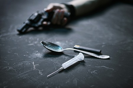 taker: Drug taker of human hand with a gun, syringe, spoon and lighter on black background