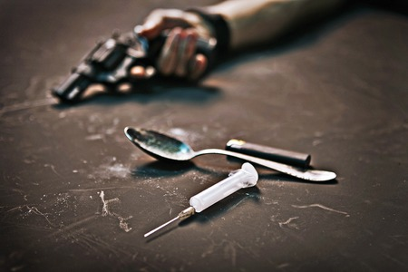 drug addiction: human hand with a gun, syringe, spoon and lighter on black background