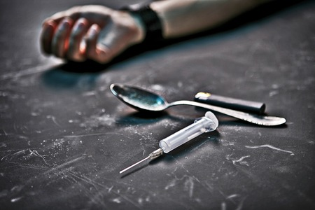 narcotism: Drug addiction photography of human hand, syringe, spoon and lighter on black background Stock Photo