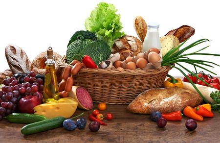 Gran variedad de alimentos en la canasta de mimbre con productos de mesa de madera vieja Foto de archivo - 25673004