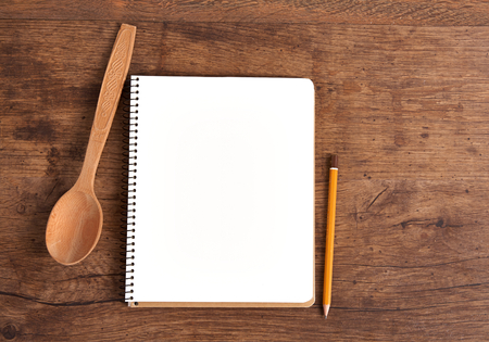 traditionary: Open cookbook, wooden kitchen spoon and pencil on wood table background