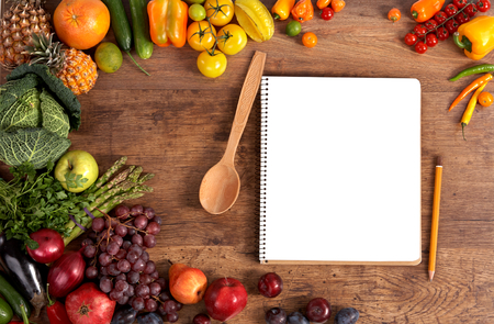 open blank ring bound notebook surrounded by a fresh vegetables and pencil on old wooden table