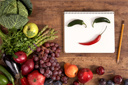 Face made of peppers in open blank ring bound notebook surrounded by a fresh vegetables and spice and pencil on old wooden table photo