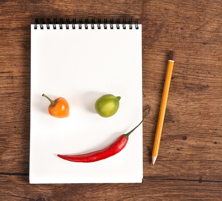 Face made of vegetables - studio photography of open blank ring bound notebook and pencil on old wooden table photo