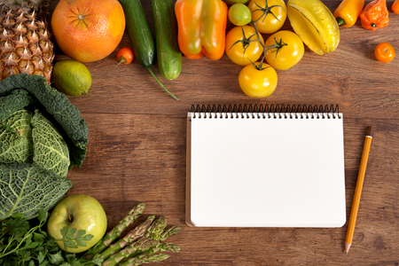 Purchase list  Space for text - studio photography of open blank ring bound notebook surrounded by a fresh vegetables and pencil on old wooden table photo