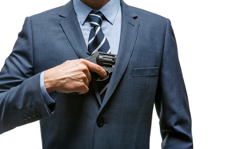 culpable: Gangster pulls out a gun - businessman pull out gun from jacket concept for aggression - isolated on white background