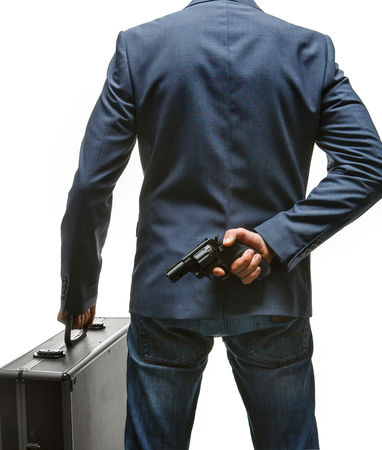 felonious: Hiding gun behind his back - studio photography of criminal man with pistol and briefcase - isolated on white background Stock Photo