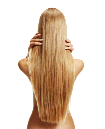 Stroking hair - studio photography of young girl with healthy long hair - isolated on white background photo