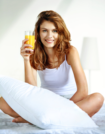 Glass of orange juice in bed - smiling brunette woman hold a glass with juice while sitting on the bed photo