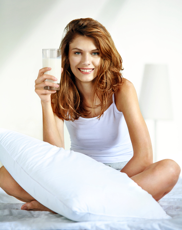 Glass of milk in bed - smiling brunette woman hold a glass with milk while sitting on the bed photo
